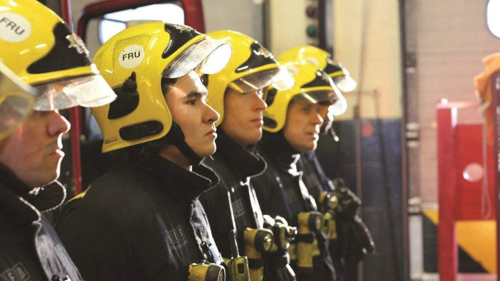 four fireman stand in a row wearing their helmuts
