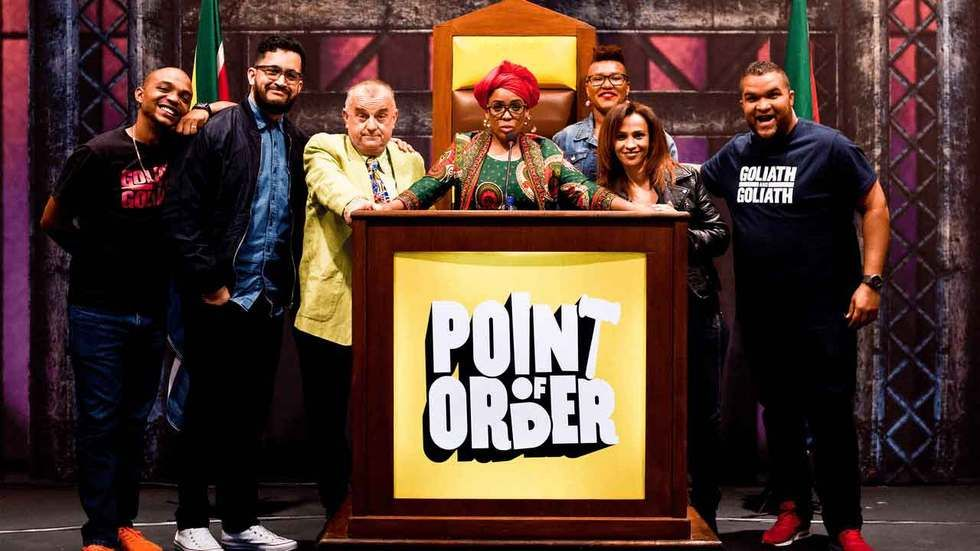 The cast of Point of Order at a podium with show logo