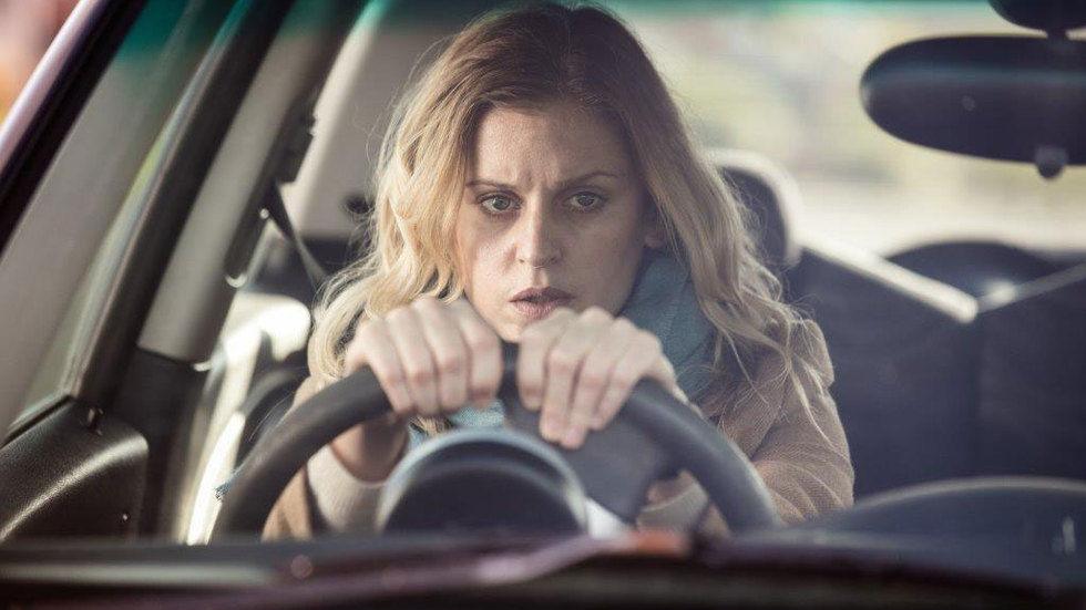 Paula behind the wheel inside car