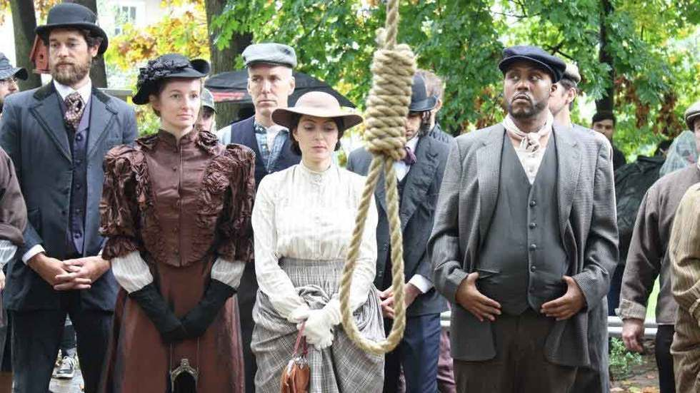 A group of people standing behind a hanging noose.