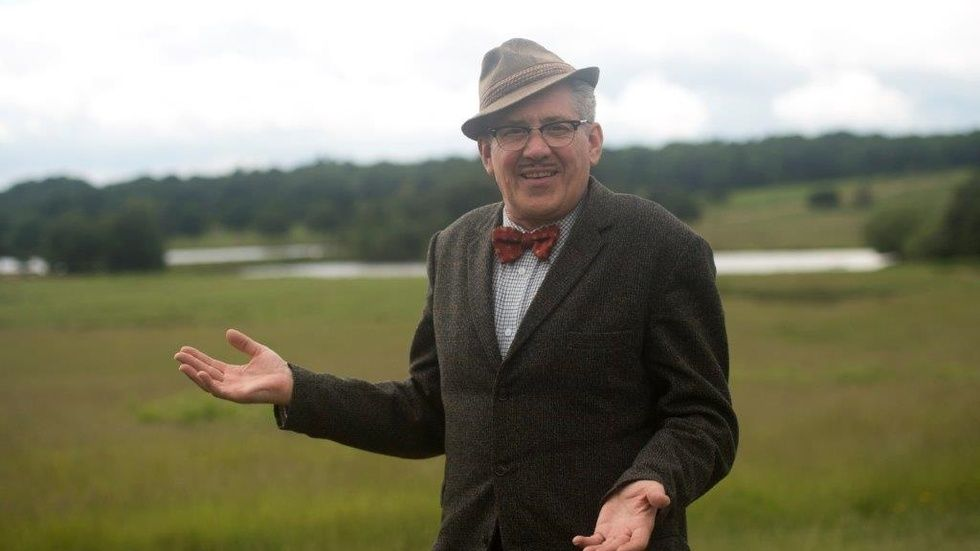 Count Arthur Strong standing in field with open arms