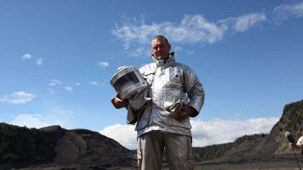 Man stands outdoors wearing a spacesuit