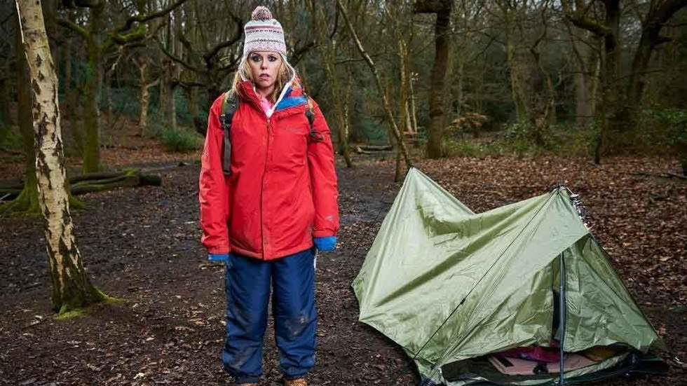 Roisin Conaty as Marcella in GameFace, standing in a forest next to a tent.