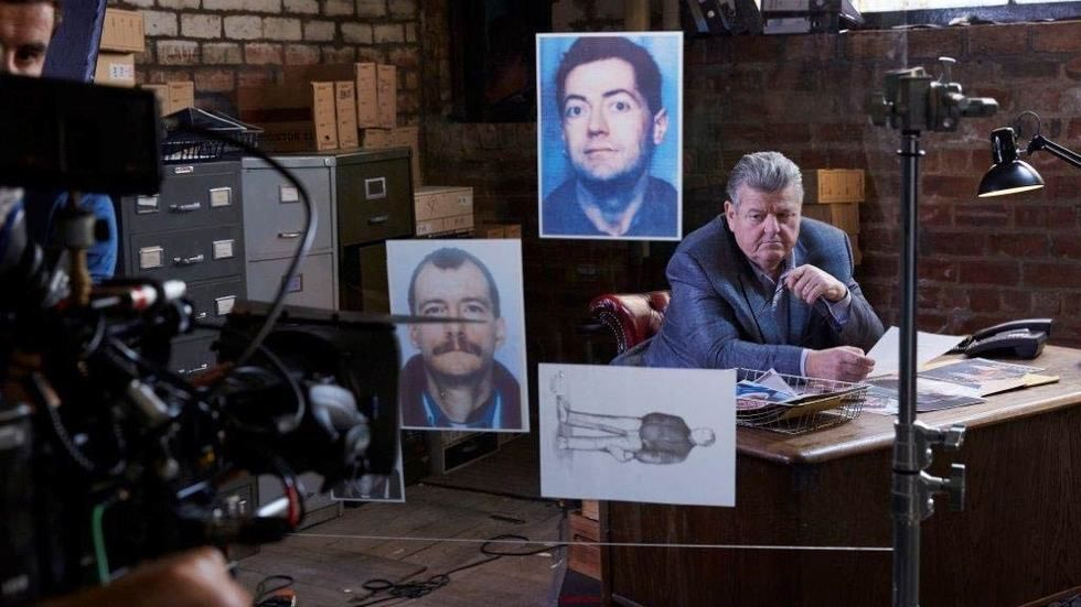 Robbie Coltrane sitting at a desk with photos, lights and cameras