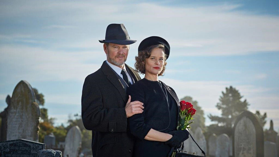 Doctor Blake and Jean with hats and roses in the cemetary