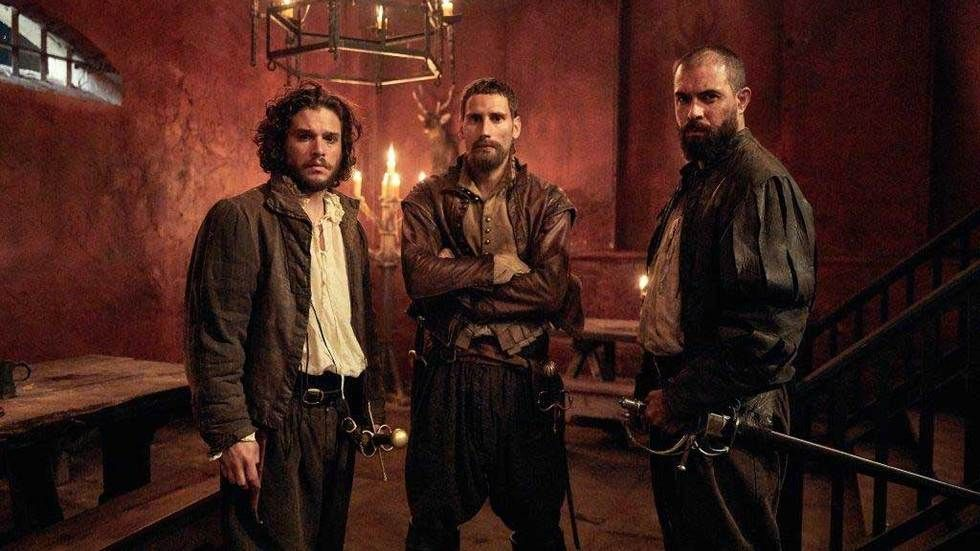Three men with swords in a candlelit room.