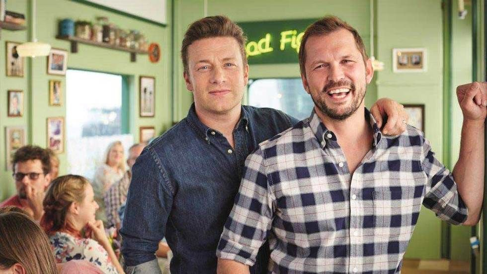Jamie Oliver and Jimmy Doherty stand in cafe and laugh