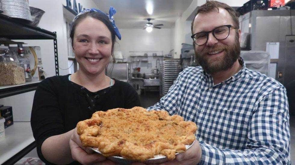Man and woman hold big pie.