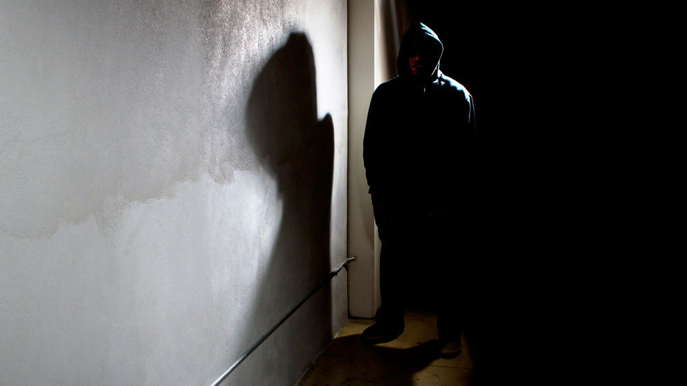 A man standing in the darkness wearing a hoodie.