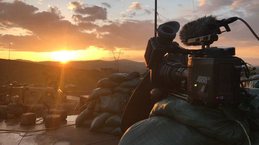 Television camera filming military operations at sunrise