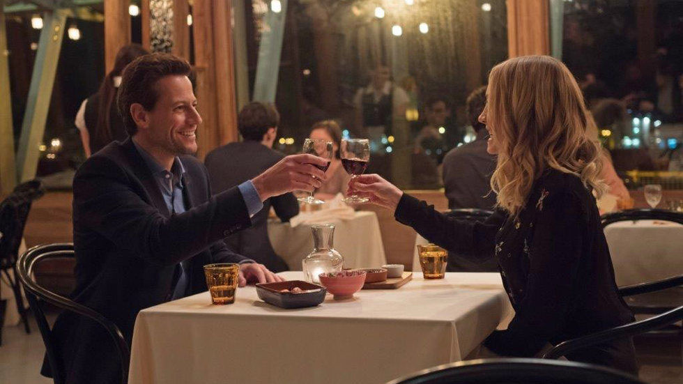 A scene from Liar, with Joanne Froggatt and Ioan Gruffudd having a drink at a restaurant table