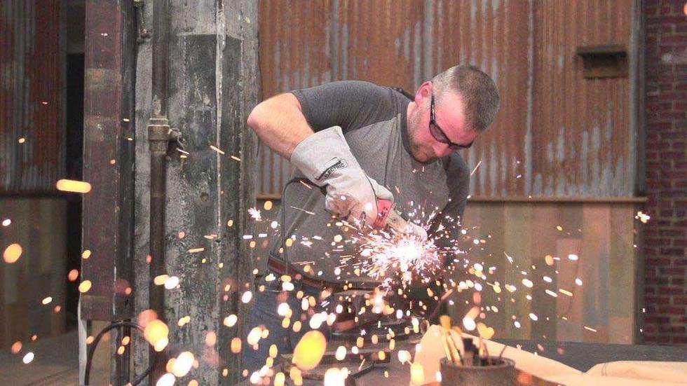 man in workshop soldering