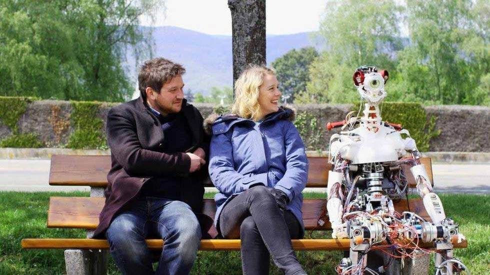 A man and a woman sitting on a bench next to a robot