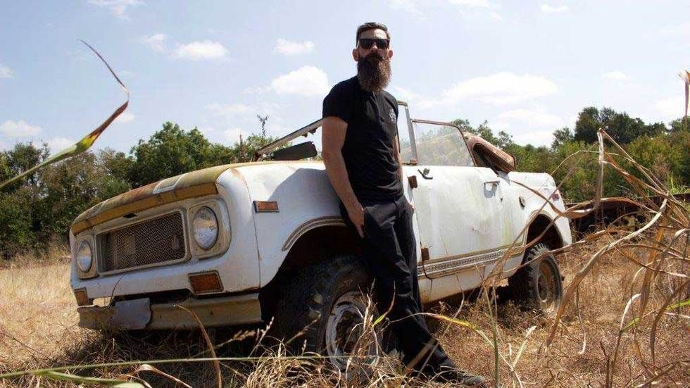 Aaron Kaufman stands against a car