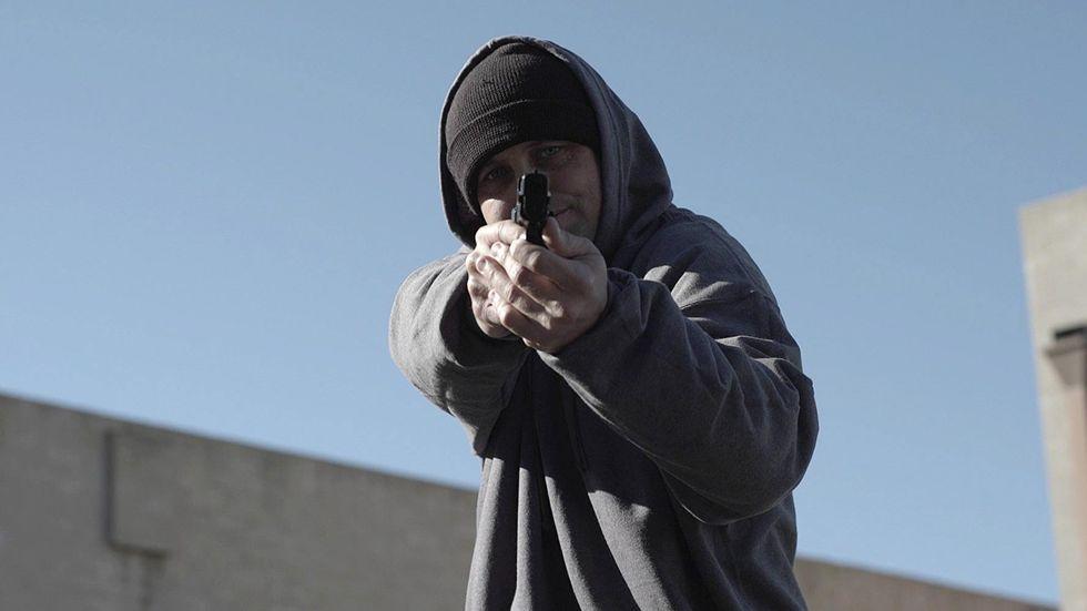 man wearing hoodie aims gun at camera