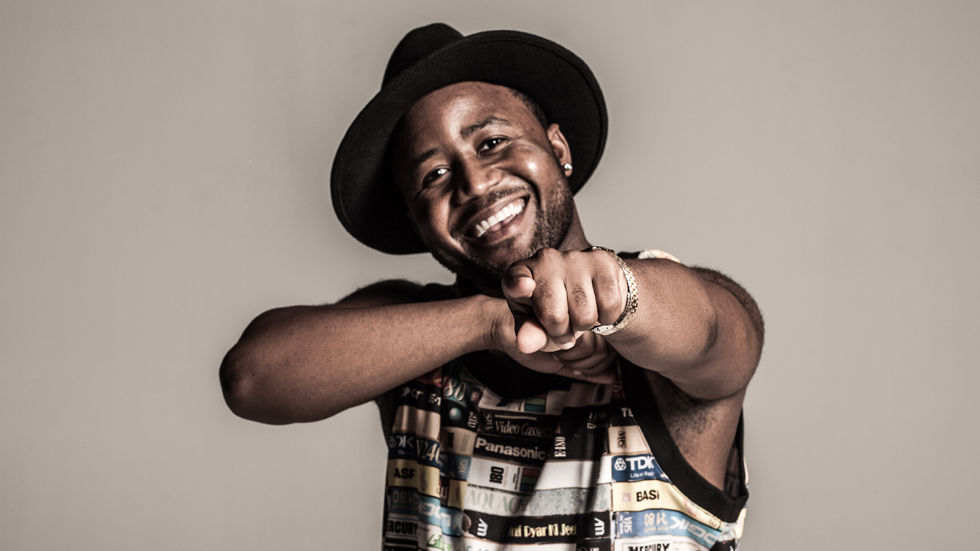 South African Rapper and Record Producer Cassper Nyovest in colourful vest with black hat, pointing towards you, smiling.