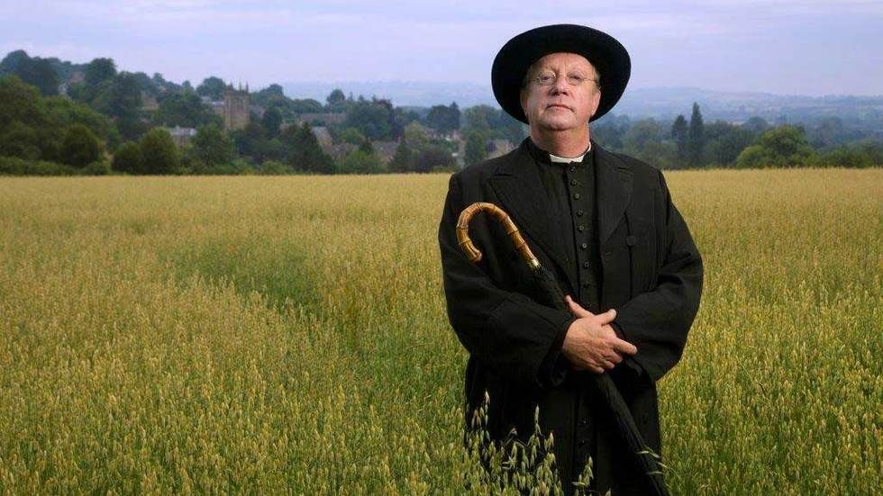 Father Brown stands in a field with his umbrella