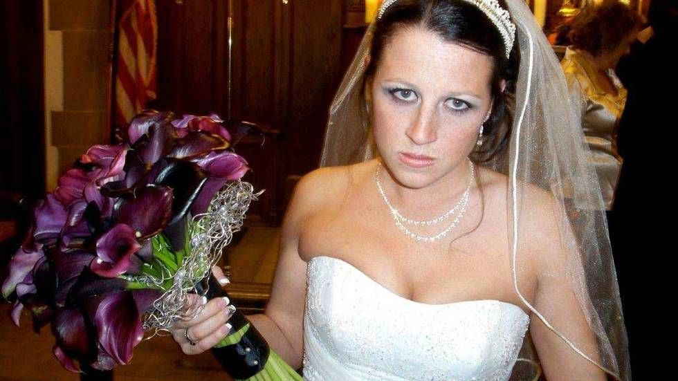 Angry bride holding bunch of flowers