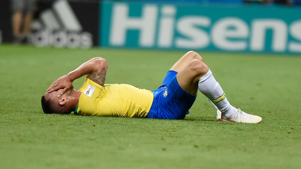 A dejected Brazilan player lays on the ground.
