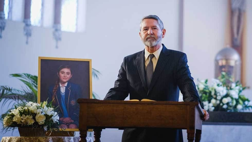 a pastor at a memorial service with the deceased in a framed photo in the background